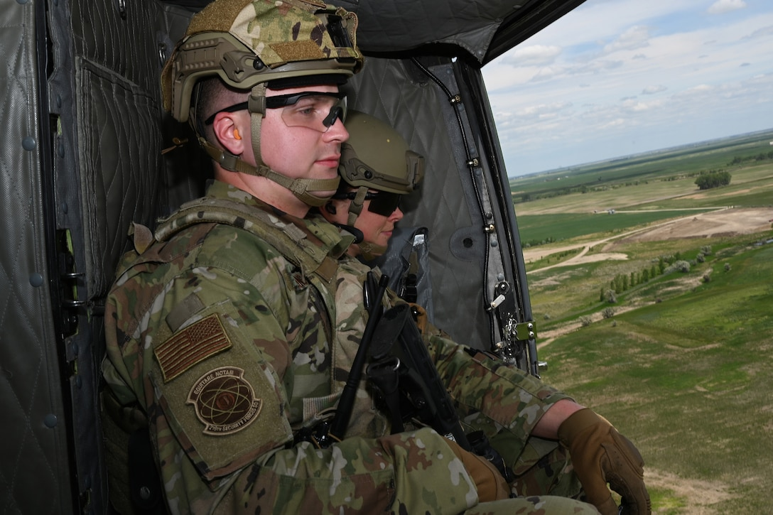 Two North Dakota Air National Guard 219 Security Forces Squadron members wearing military uniforms sit in a UH-1N Huey helicopter, looking out an open door, as they fly over a rural area near the Minot Air Force Base, N.D., June 24, 2021.