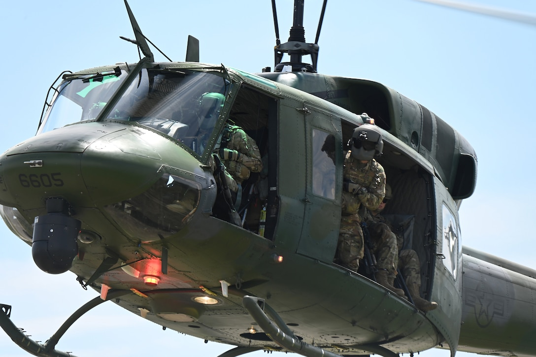 A three-person crew of a 54th Helicopter Squadron operate a UH-1N Huey helicopter as the flight engineer peers out an open door while watching the ground for landing during a training exercise at the Minot Air Force Base, N.D., June 24, 2021.