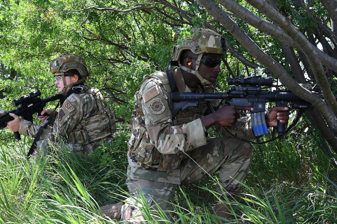 Two North Dakota Air National Guard members of the 219th Security Forces Squadron in uniform crouch near some bushes with training M4 rifles during a training exercise at the Minot Air Force Base, N.D., June 24, 2021.