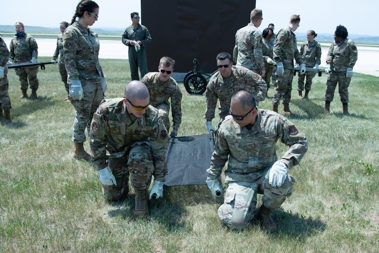 Members of the 28th Medical Group rehearse lifting a litter as a cohesive unit for exercise Golden Coyote on Ellsworth Air Force Base, S.D., June 16, 2021.