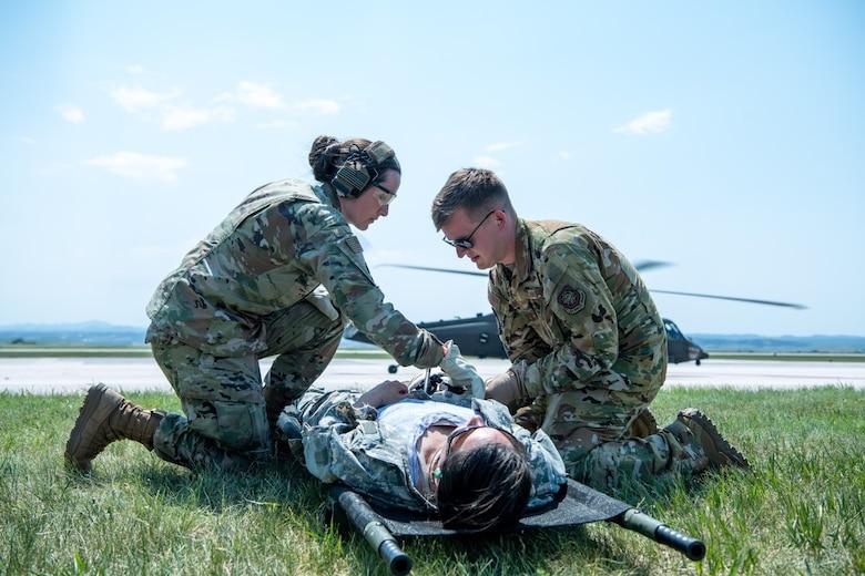 "Capt. John Innins, a 375th Aeromedical Evacuation Squadron flight nurse, and Master Sgt. Amanda Tokarczyk, the 28th Operational Medical Readiness Squadron aerospace medicine flight chief, assist a ""patient"" on Ellsworth Air Force Base, S.D., June 16, 2021."