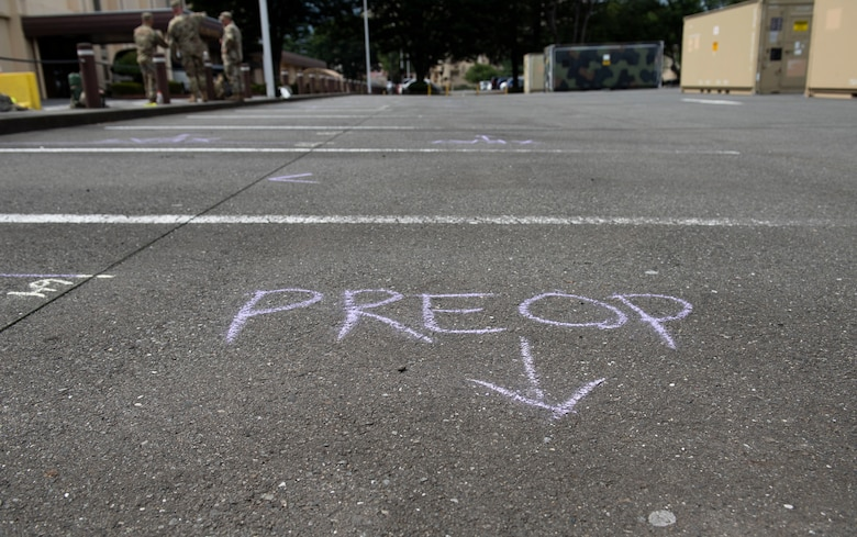 A chalk mark made by a 311th Field Hospital soldier from Blacklick, Ohio, indicates a spot for a medical tent during an Army field exercise at Yokota Air Base, Japan, June 24, 2021. When deployed the field hospital would be fully functional and come with a lab, intermediate care wards, X-ray, pharmacy and central medical supplies. (U.S. Air Force photo by Senior Airman Hannah Bean)