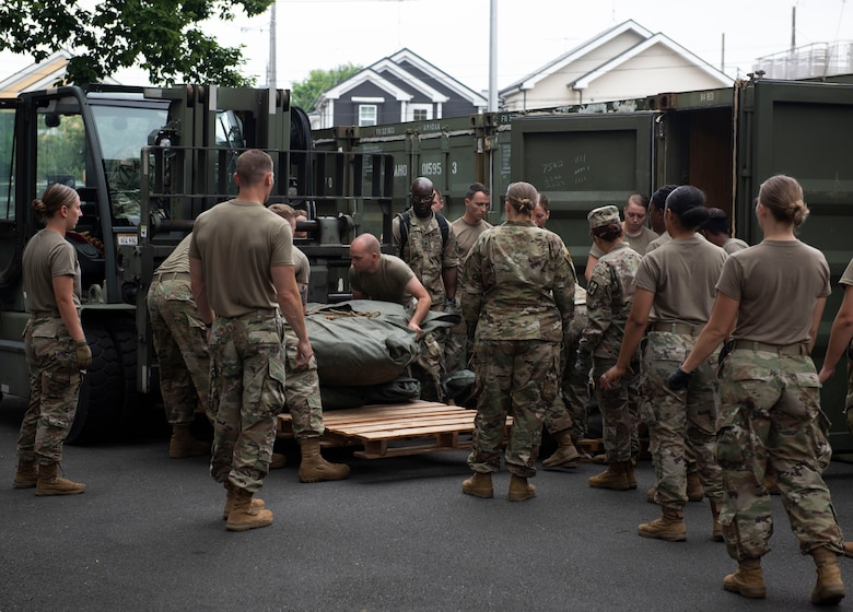 Soldiers from the 311th Field Hospital from Blacklick, Ohio, load materials on to a pallet prior to building a mock deployment hospital for an Army field exercise at Yokota Air Base, Japan, June 25, 2021. When deployed the field hospital would be fully functional and come with a lab, intermediate care wards, X-ray, pharmacy and central medical supplies. (U.S. Air Force photo by Senior Airman Hannah Bean)