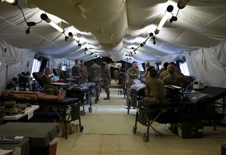 Soldiers from the 311th Field Hospital from Blacklick, Ohio, relax after setting up a 32-bed hospital during an Army field exercise at Yokota Air Base, Japan, June 25, 2021. During the exercise, the soldiers performed a variety of simulated procedures to include installing IVs, providing sutures and opening airways. (U.S. Air Force photo by Senior Airman Hannah Bean)