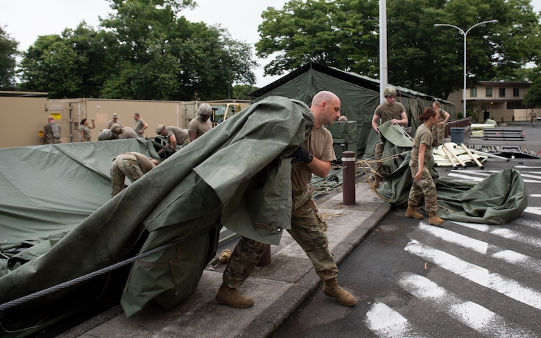 Soldiers from the 311th Field Hospital from Blacklick, Ohio, moves a tent tarp after an Army field exercise at Yokota Air Base, Japan, June 25, 2021. With the assistance of the 18th Medical Command and the 374th Airlift Wing, the 311th Field Hospital received the opportunity to mock forward deploy and practice setting up a 32-bed hospital in an unfamiliar location. (U.S. Air Force photo by Senior Airman Hannah Bean)