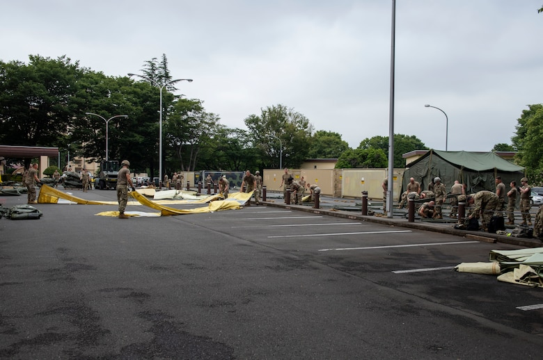 Soldiers from the 311th Field Hospital from Blacklick, Ohio, break down various equipment after an Army field exercise at Yokota Air Base, Japan, June 25, 2021. With the assistance of the 18th Medical Command and the 374th Airlift Wing, the 311th Field Hospital received the opportunity to mock forward deploy and practice setting up a 32-bed hospital in an unfamiliar location. (U.S. Air Force photo by Senior Airman Hannah Bean)