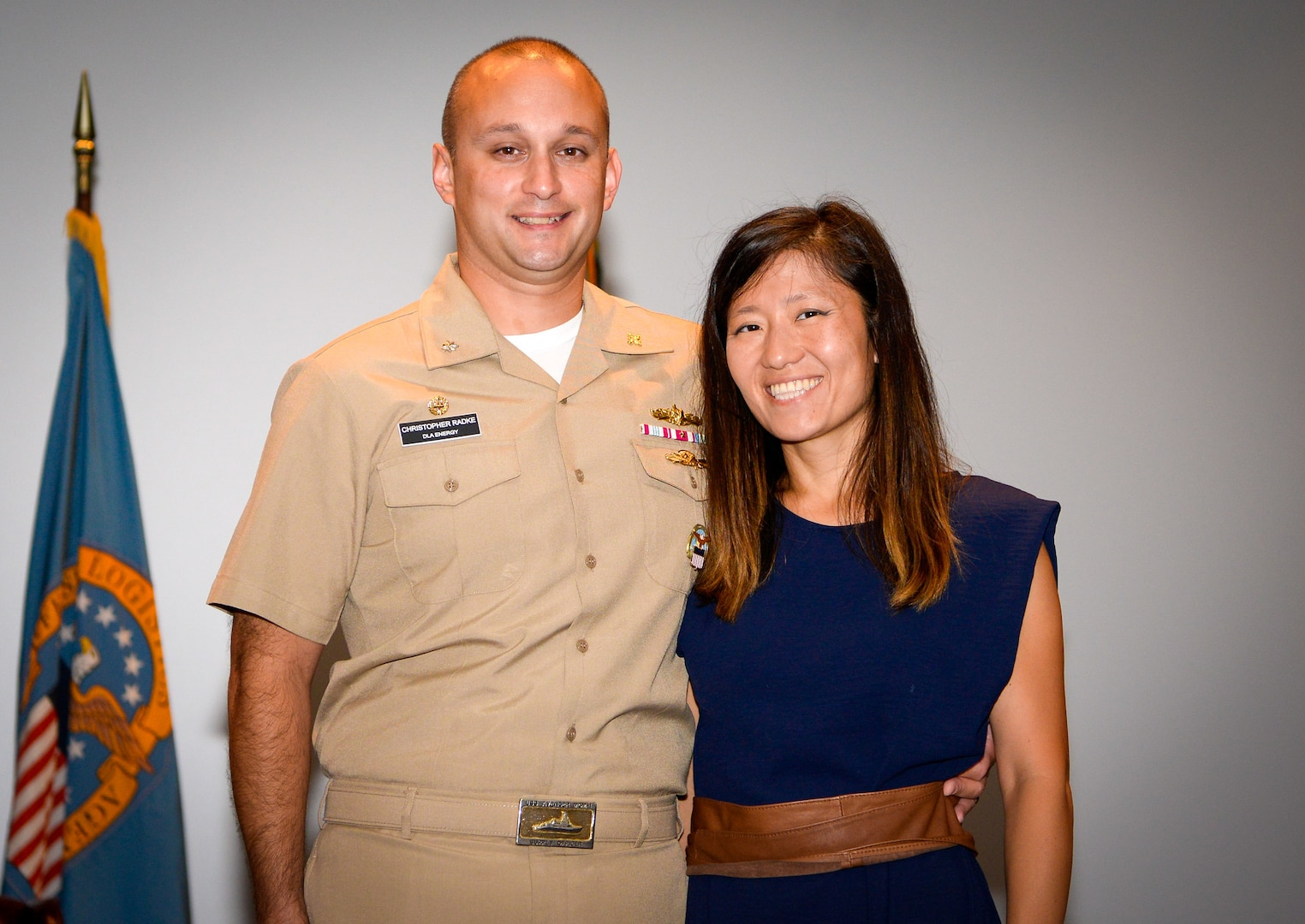 A Navy officer stands with his wife