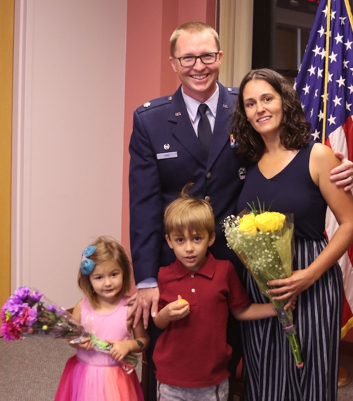 An Air Force officer stands with his family
