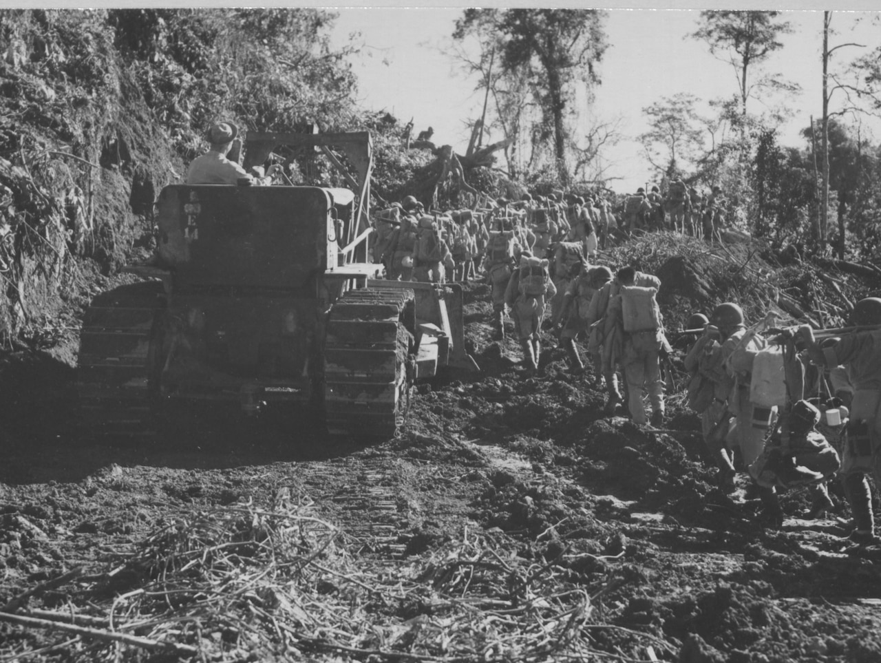 A line of soldiers walks past a large tractor that's working to clear a dirt road.