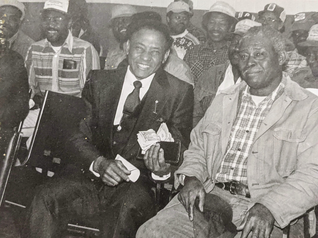 Several men sit grouped together. One smiles while holding up a wallet spilling over with cash.