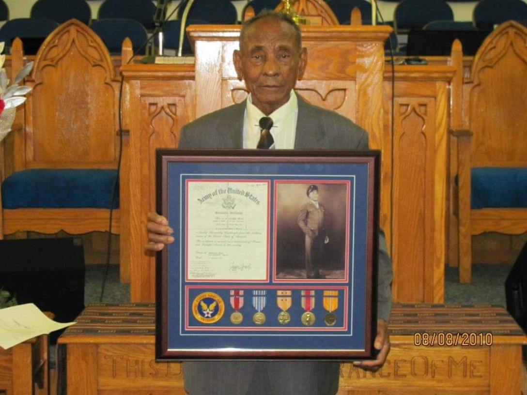An older man standing in front of a lectern  holds a plaque.
