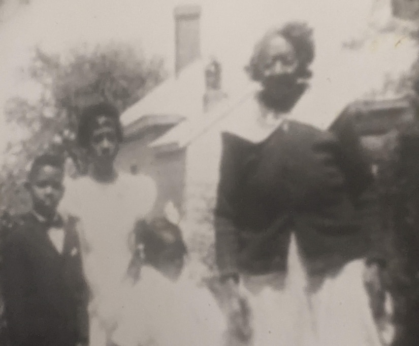A boy, two girls and a woman pose for a photo in front of a house.