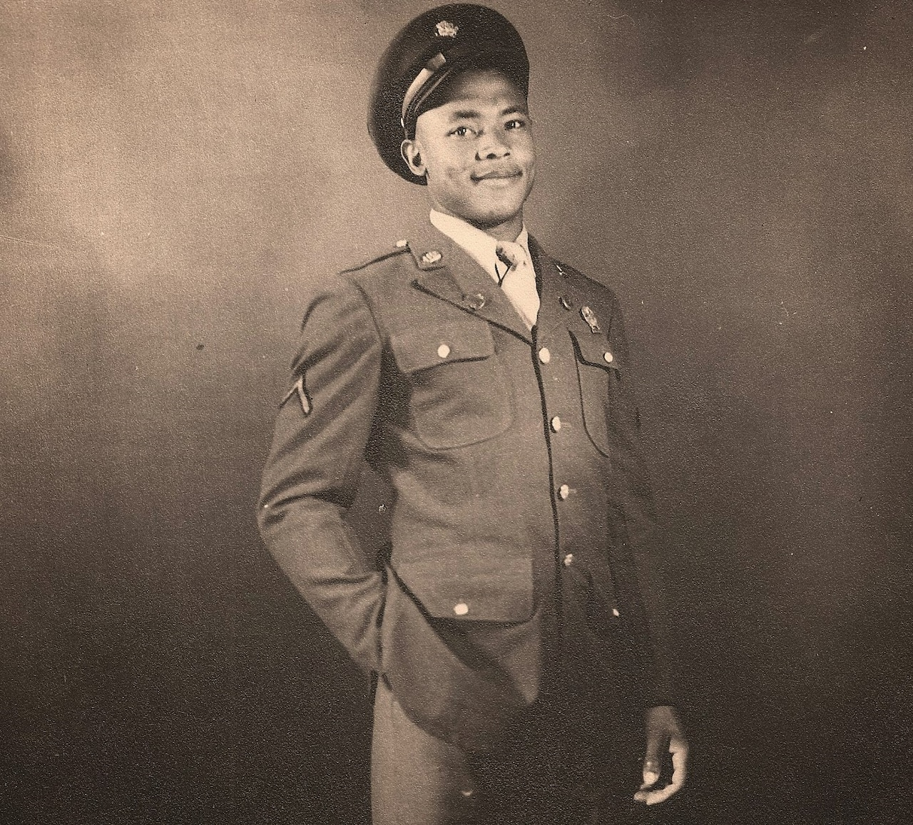 A man in a uniform and cap poses for a photo with one hand in his pocket.