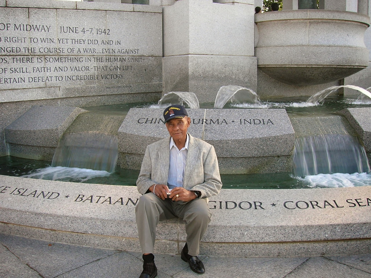 A man wearing a suit and baseball cap sits in front of a water fountain monument.