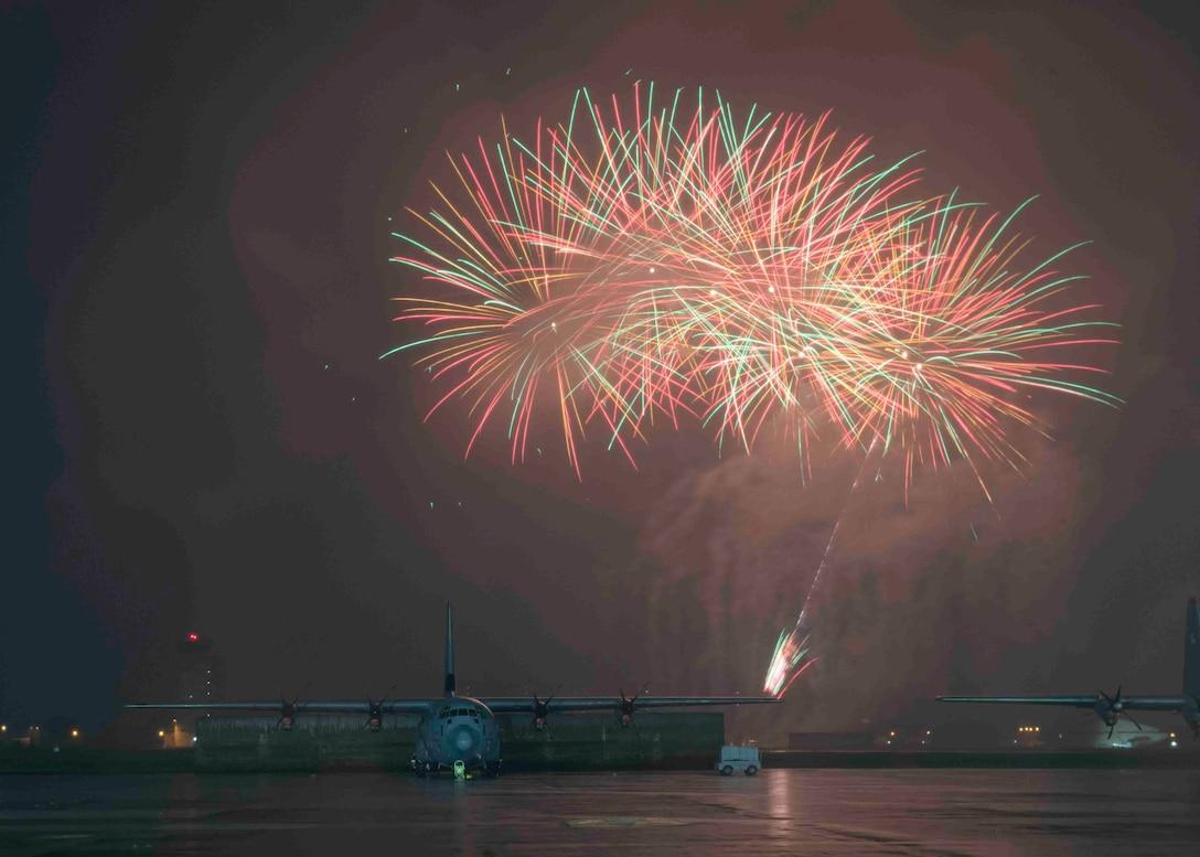 Fireworks explode behind a C-130J Super Hercules during a celebrate America at Yokota Air Base, Japan, July 2, 2021.