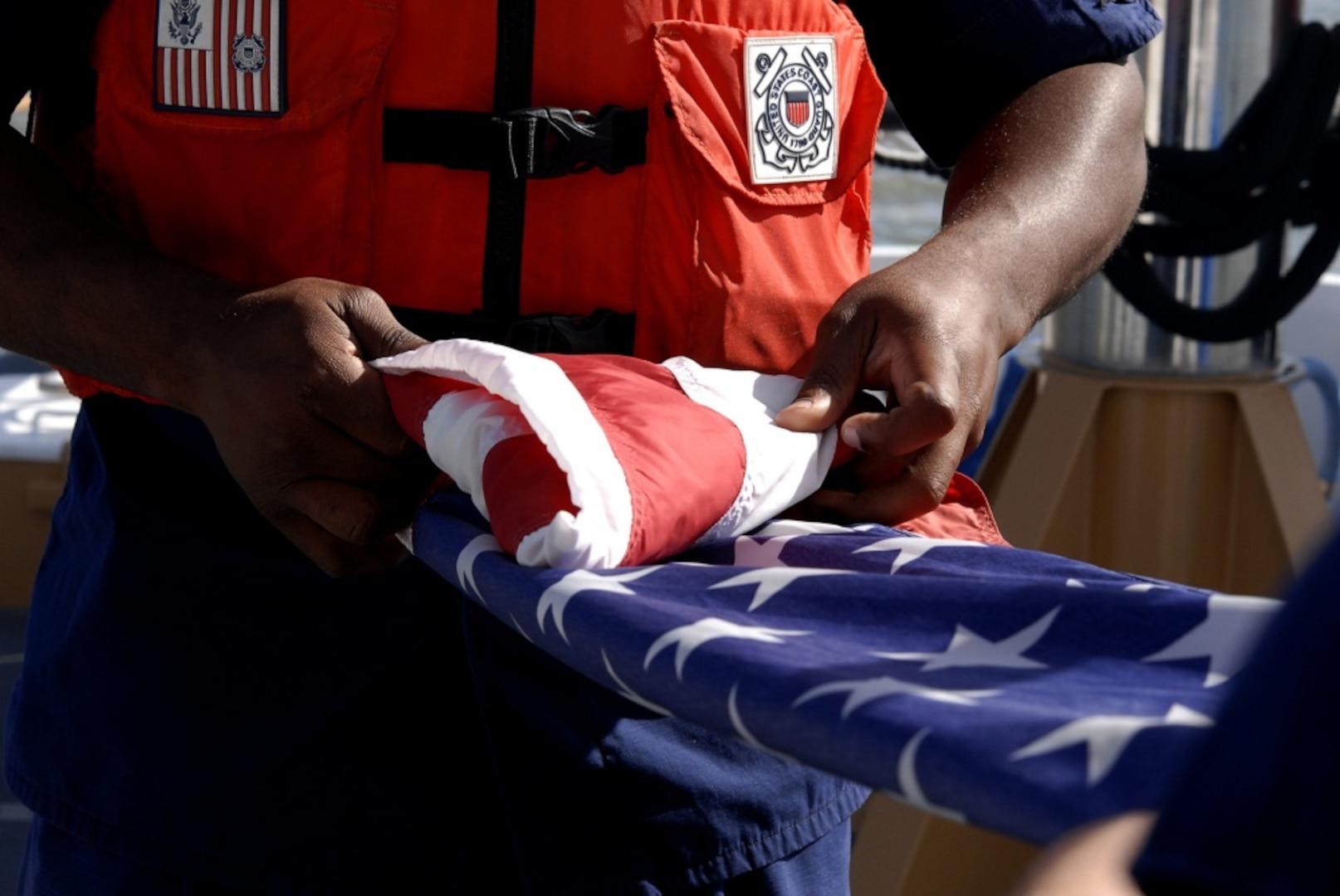 Coast Guard member folds National Ensign
