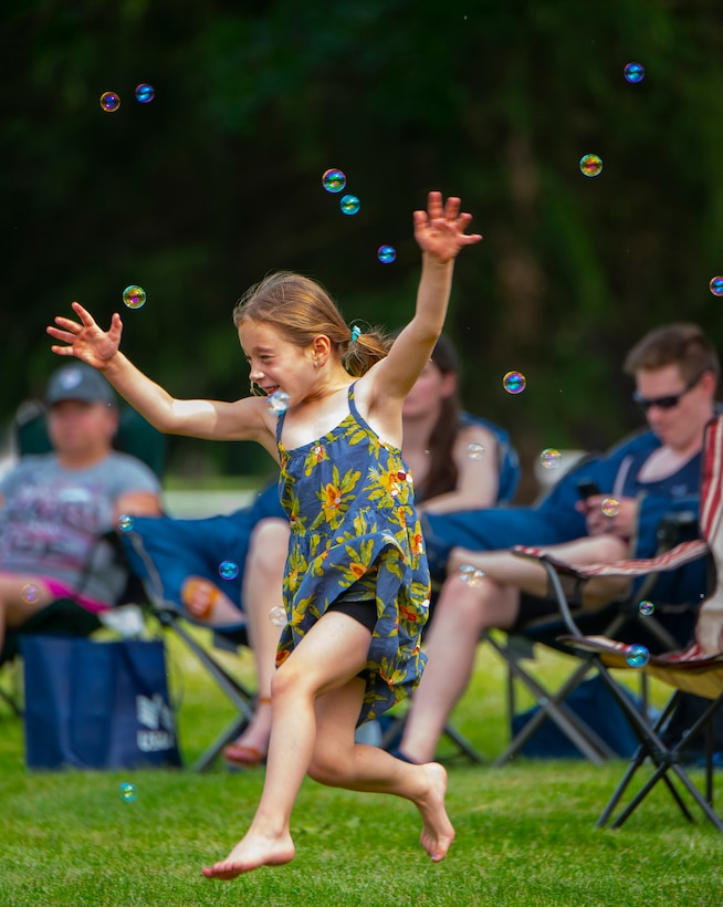 Alexandra Burger, 6, daughter of Col. Paul Burger, dances and chases bubbles June 24, 2021, at a block party sponsored by the 88th Force Support Squadron at Turtle Pond in the brick quarters historic district at Wright-Patterson Air Force Base, Ohio. The party, the first of a series of three through the summer, was free to all members of the Wright-Patt community. (U.S. Air Force photo by R.J. Oriez)