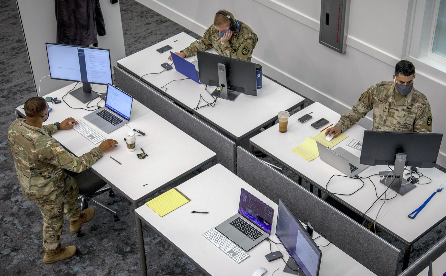 Photo of servicemembers on computers.