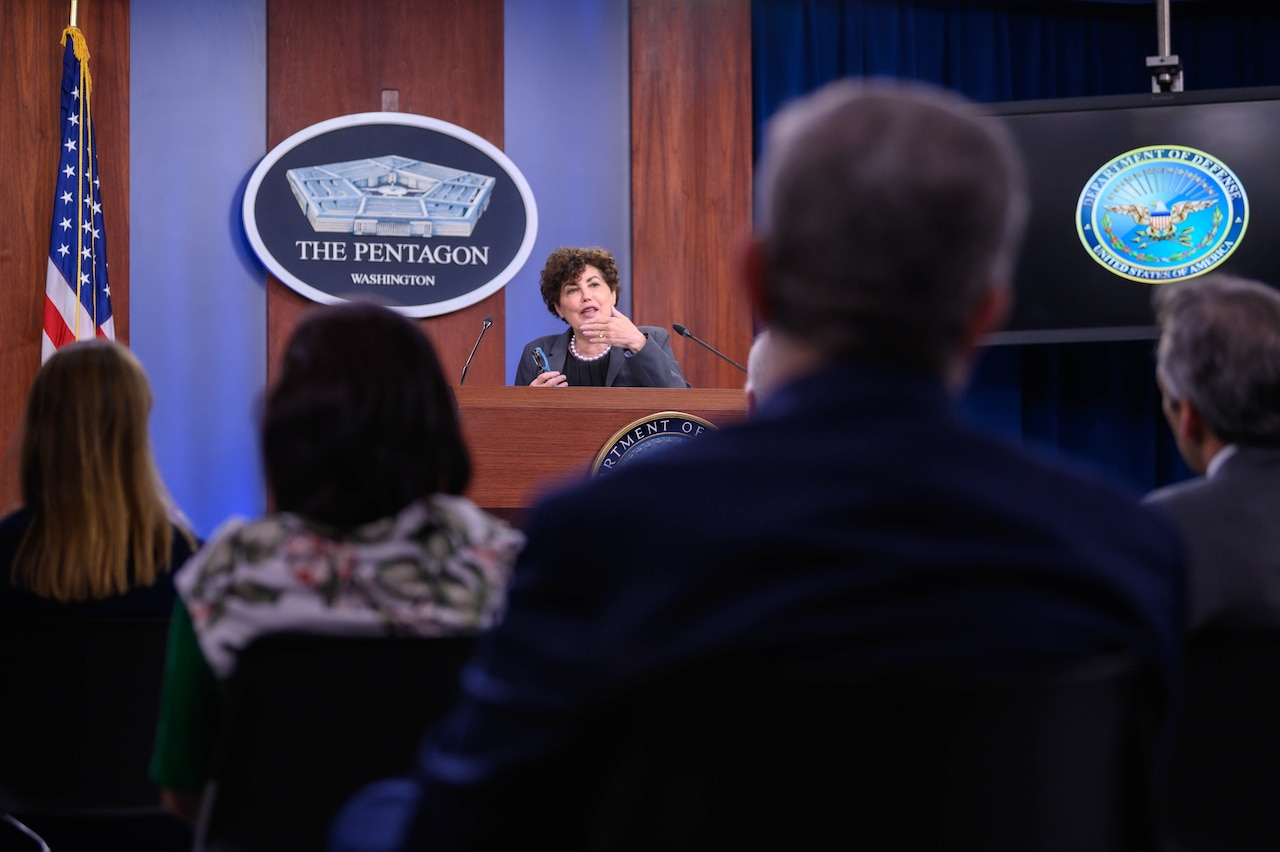 A woman stands behind a lectern. Before her is an audience of reporters.