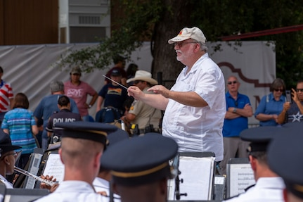 """Retired U.S. Army Chief Warrant officer 4 Charles Booker, bandmaster for 5th Army Band from 1972-1976, leads """"Fort Sam's Own"""" 323d Army Band and 313th Army Band, a U.S. Army Reserve band during an Independence Day concert held at The Alamo, July 2, 2021. Booker was spontaneously asked to lead the concert during the last song, """"Stars and Stripes Forever."""" (U.S. Army Photo by Bethany Huff)"""