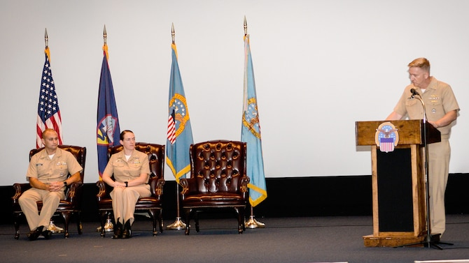 Three Navy officers on a stage