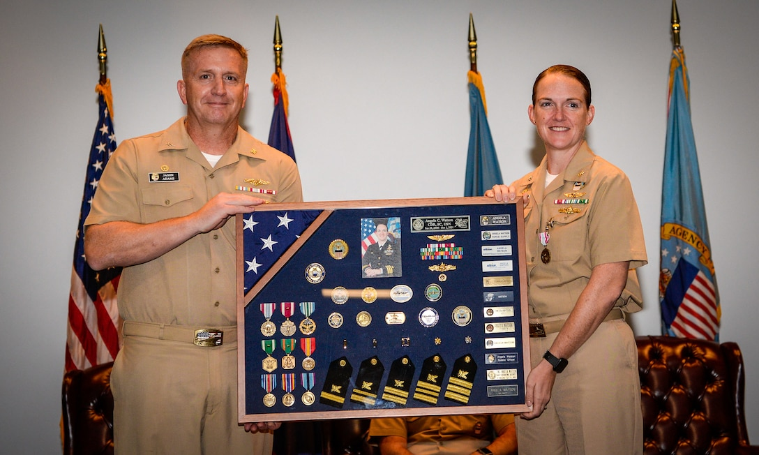 Two people in Navy khaki uniforms hold a large military shadow box