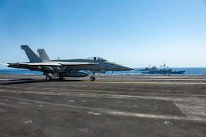 """An F/A-18E Super Hornet fighter jet, attached to the """"Rampagers"""" of Strike Fighter Squadron (VFA) 83, lands on the flight deck of aircraft carrier USS Dwight D. Eisenhower (CVN 69) as the ship conducts a passing exercise with guided-missile cruiser USS Vella Gulf (CG 72), left, and Egyptian Navy guided-missile frigate ENS Taba (FFG 916) in the Red Sea, June 29. The Eisenhower Carrier Strike Group is deployed to the U.S. 5th Fleet area of operations in support of naval operations to ensure maritime stability and security in the Central Region, connecting the Mediterranean and Pacific through the western Indian Ocean and three strategic choke points."""