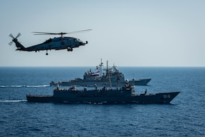 """An MH-60R Sea Hawk helicopter, attached to the """"Swamp Foxes"""" of Helicopter Maritime Strike Squadron (HSM) 74, flies above Egyptian Navy guided-missile frigate ENS Taba (FFG 916), front, and guided-missile cruiser USS Vella Gulf (CG 72) during a passing exercise with aircraft carrier USS Dwight D. Eisenhower (CVN 69), not pictured, in the Red Sea, June 29. The Eisenhower Carrier Strike Group is deployed to the U.S. 5th Fleet area of operations in support of naval operations to ensure maritime stability and security in the Central Region, connecting the Mediterranean and Pacific through the western Indian Ocean and three strategic choke points."""