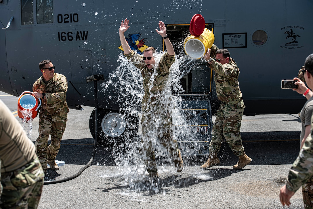 """Members of the 386th Air Expeditionary Wing dump coolers of ice water on Col. Philip Shea, 407th Air Expeditionary Group commander, after his """"fini flight"""" at Ali Al Salem Air Base, Kuwait, July 4, 2021."""