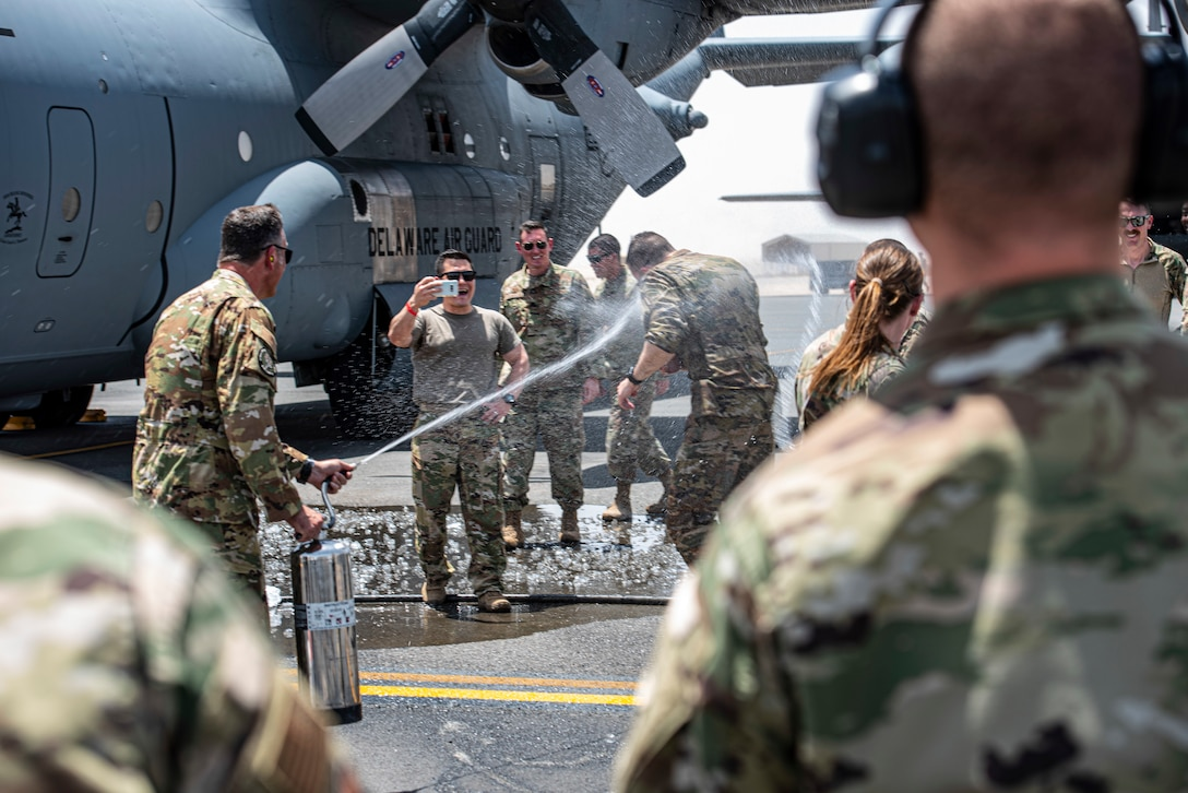 """Members of the 386th Air Expeditionary Wing hose down Col. Philip Shea, 407th Air Expeditionary Group commander, after his """"fini flight"""" at Ali Al Salem Air Base, Kuwait, July 4, 2021"""