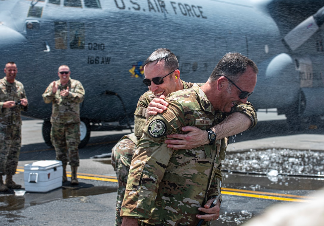 U.S. Air Force Col. Philip Shea, 407th Air Expeditionary Group commander, hugs Col. Micheal Moeding, Director of Mobility Forces, U.S. Air Forces Central, on the flight line at Ali Al Salem Air Base, Kuwait, July 4, 2021.