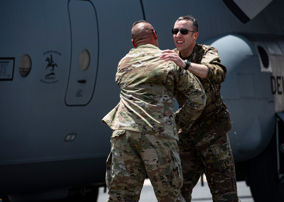 U.S. Air Force Col. Philip Shea, 407th Air Expeditionary Group commander, receives a hug on the flight line at Ali Al Salem Air Base, Kuwait, July 4, 2021