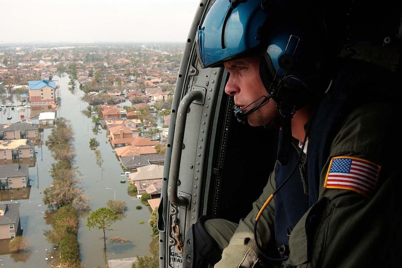 A person looks out of a helicopter at flooding.