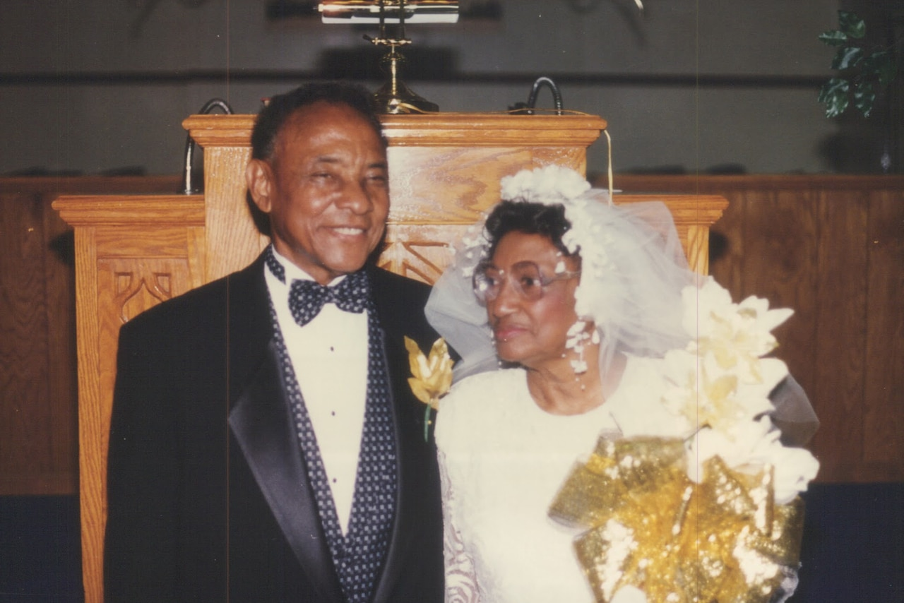 An older couple poses for a photo in wedding attire.