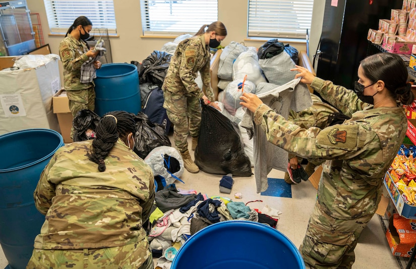 Airmen from the 432nd Maintenance Squadron sort through clothing donations.
