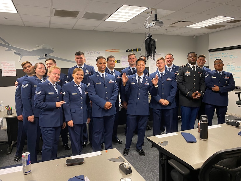 Classmates from ALS Class 21-4 gather to take a photo in their dress blues on Shaw Air Force Base, S.C., April 22, 2021. Airman Leadership School prepares service members and civilians  to become team leaders and frontline supervisors that help better our military.