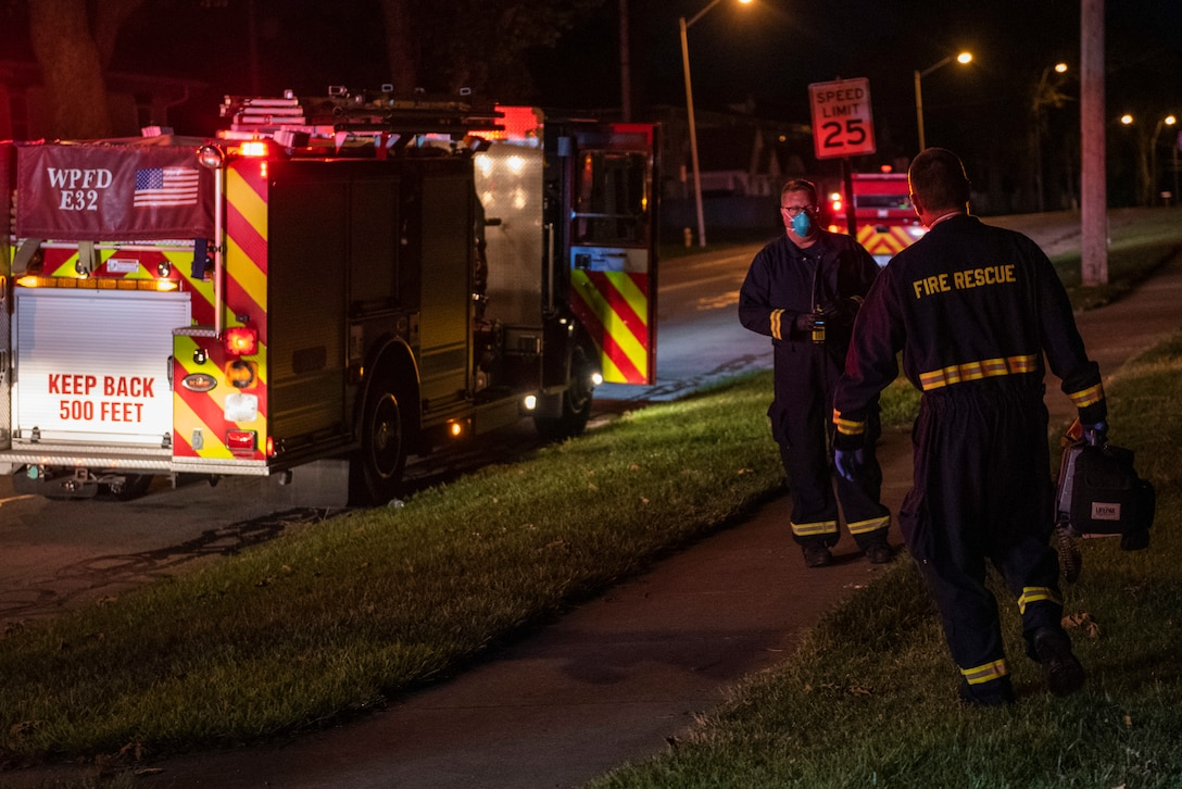 Firefighters return to their truck after responding to a call for medical help in base housing, June 23, 2021 at Wright-Patterson Air Force Base, Ohio.  The base has three stations strategically located to ensure a response time of 5 minutes or less when the call comes in. (U.S. Air Force photo by Wesley Farnsworth)