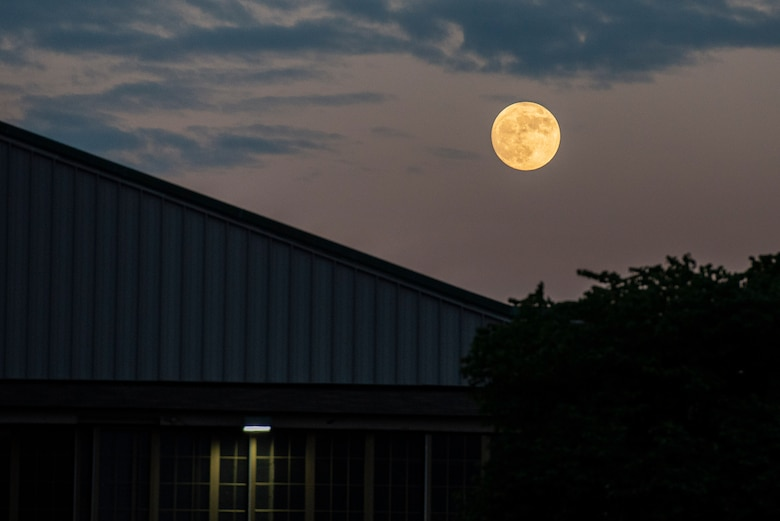 A nearly full moon lights up the sky over a building at Wright-Patterson Air Force Base, Ohio, June 23, 2021. The base has three fire stations strategically located to ensure a response time of 5 minutes or less when the call comes in. (U.S. Air Force photo by Wesley Farnsworth)