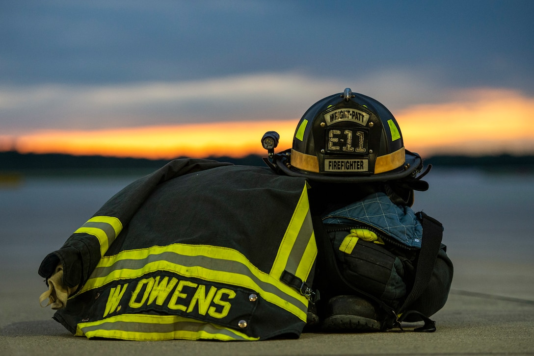 Bunker gear sits staged just outside the bays of Fire Station 1 for a sunset photo, June 23, 2021 at Wright-Patterson Air Force Base, Ohio.  The base has three stations strategically located to ensure a response time of 5 minutes or less when the call comes in. (U.S. Air Force photo by Wesley Farnsworth)