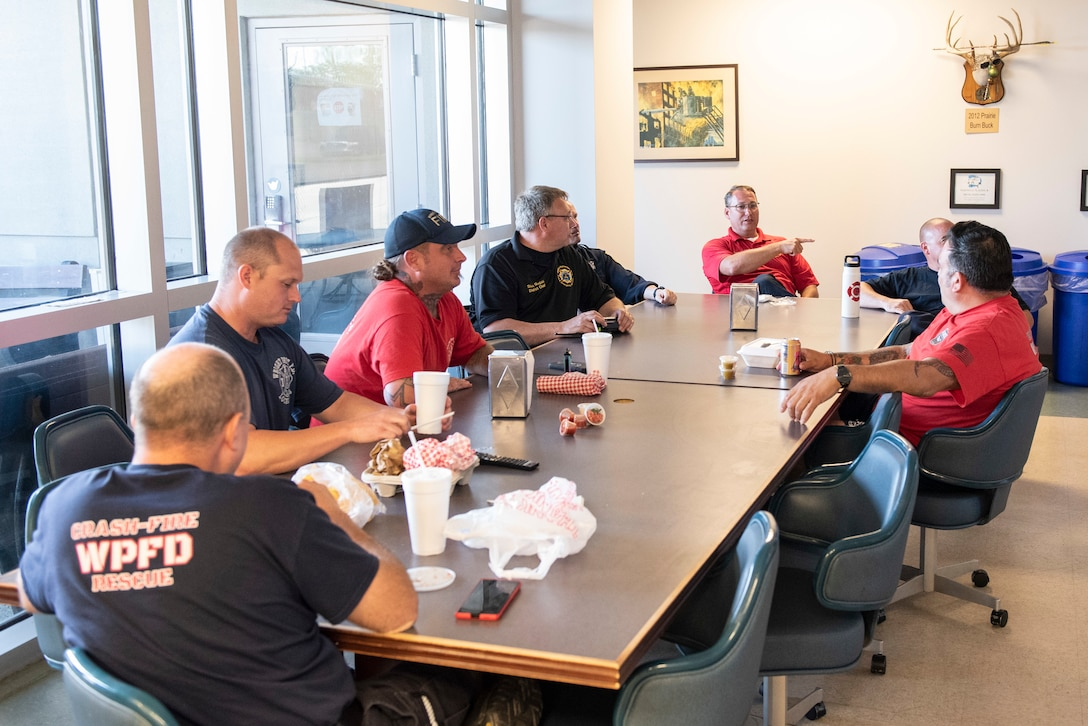 Firefighters with the 788th Civil Engineer Squadron Fire Department sit down for dinner inside Station 1, June 23, 2021, at Wright-Patterson Air Force Base, Ohio. The fire department is on call 24/7 all year and capable of responding anywhere on base within 5 minutes when a call for help comes in. (U.S. Air Force photo by Wesley Farnsworth)