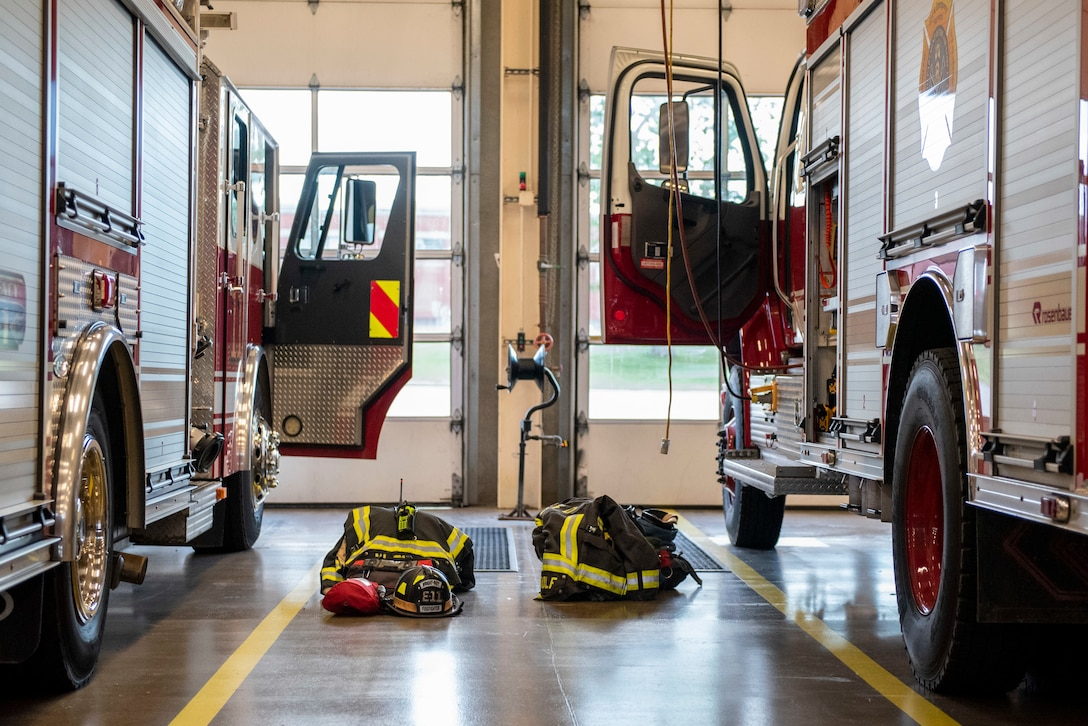 Bunker gear sits staged next to two fire trucks belonging to the 788th Civil Engineer Fire Department inside the bays at Station 1, June 23, 2021, at Wright-Patterson Air Force Base, Ohio. The fire department is on call 24/7 all year and capable of responding anywhere on base within 5 minutes when a call for help comes in. (U.S. Air Force photo by Wesley Farnsworth)