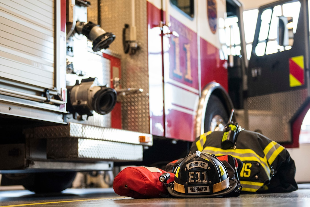Bunker gear sits staged next to a fire truck belonging to the 788th Civil Engineer Fire Department inside the bays at Station 1, June 23, 2021, at Wright-Patterson Air Force Base, Ohio. The fire department is on call 24/7 all year and capable of responding anywhere on base within 5 minutes when a call for help comes in. (U.S. Air Force photo by Wesley Farnsworth)