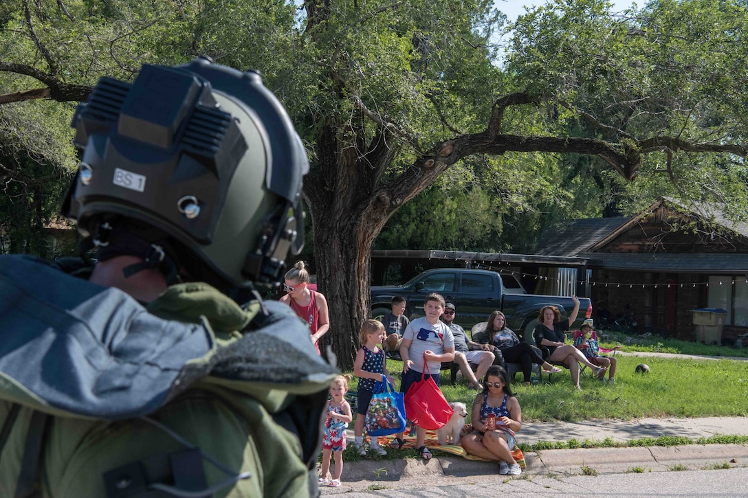 Master Sgt. John Wawrzynski, 22nd Civil Engineer Squadron explosive ordnance disposal flight superintendent, waves to parade attendees during the Derby Independence Day parade July 3, 2021, in Derby, Kansas. Wawrzynski displayed a blast-proof body suit and helmet weighing approximately 96 pounds throughout the parade. (U.S. Air Force photo by Senior Airman Marc A. Garcia)