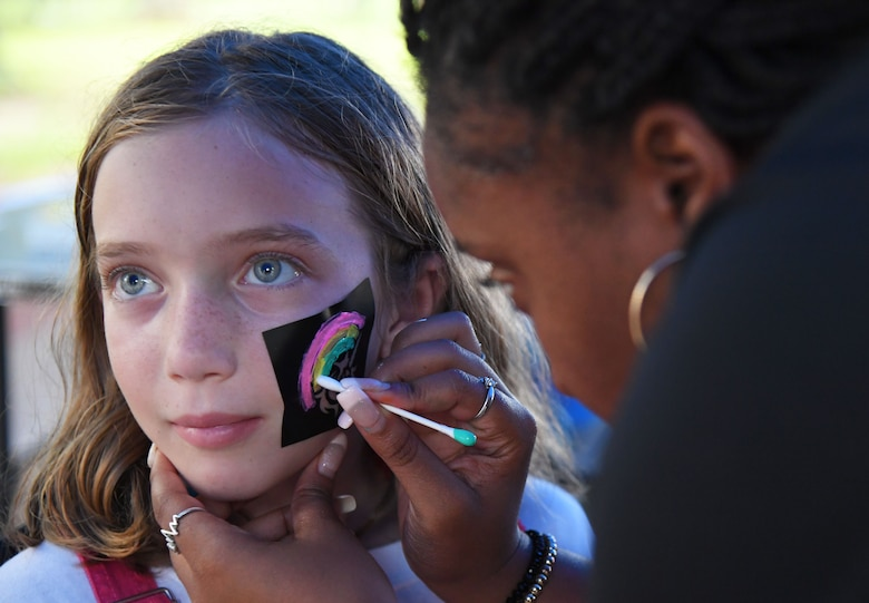 TaNessa Scott, 81st Force Support Squadron recreation assistant, applies face paint to Sidney Estridge, daughter of U.S. Air Force Col. Chris Estridge, 81st Medical Group commander, during Freedom Fest at Marina Park at Keesler Air Force Base, Mississippi, July 2, 2021. The event also included hot wings and watermelon eating competitions and fireworks. (U.S. Air Force photo by Kemberly Groue)