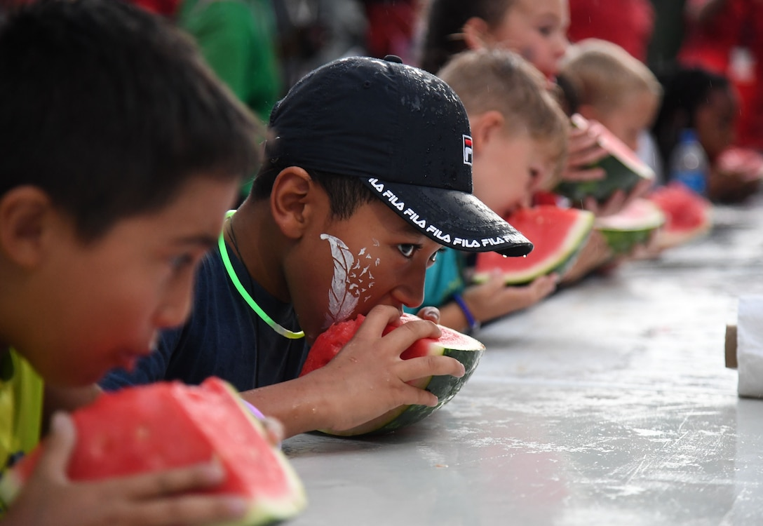 Katavion Brown, son of U.S. Navy Culinary Specialist Kevin Brown, Naval Construction Battalion Center Gulfport senior chief, participates in a watermelon eating contest during Freedom Fest at Marina Park at Keesler Air Force Base, Mississippi, July 2, 2021. The event also included hot dogs and wings eating competitions and fireworks. (U.S. Air Force photo by Kemberly Groue)