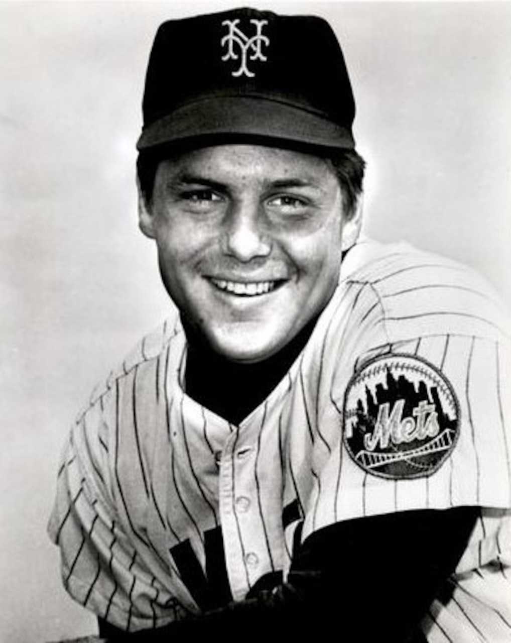 A baseball player smiles for the camera.