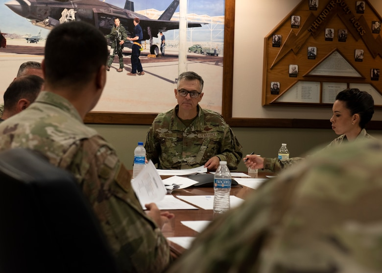 U.S. Air Force Maj. Gen. Craig Wills, center, 19th Air Force commander, and U.S. Air Force Chief Master Sgt. Kristina Rogers, 19th AF command chief, speak with Airmen assigned to the 56th Fighter Wing Fighter Country Spark team about potential innovative initiatives, June 29, 2021, at Luke Air Force Base, Arizona. Leadership from the 19th AF visited Luke AFB to engage with 56th Fighter Wing members while gaining a better understanding of the successes and challenges faced by the wing. The 56th FW's mission is to train the world's greatest fighter pilots and combat-ready Airmen. (U.S. Air Force photo by Tech. Sgt. Franklin R. Ramos)
