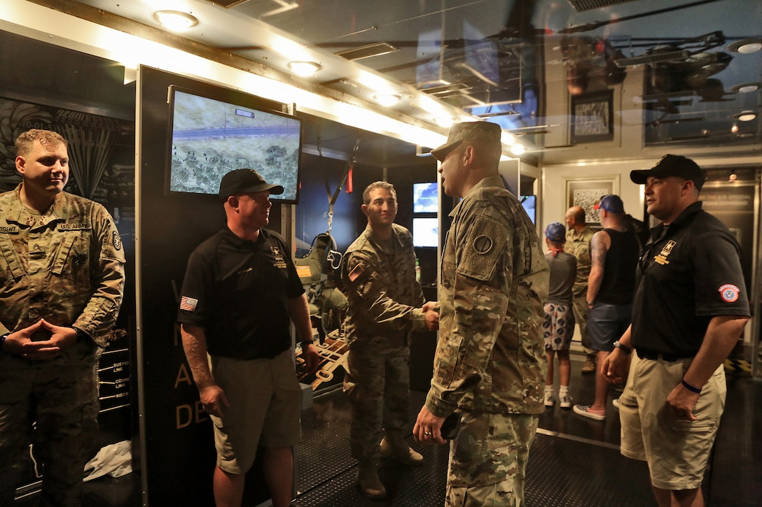 Brig. Gen. Ernest Litynski, center, Commanding General, 85th U.S. Army Reserve Support Command, receives a tour of the U.S. Army Special Operations display trailer from recruiters assigned to the U.S. Army Recruiting Battalion-Milwaukee during the Fourth of July NASCAR Cup Series race at Road America, Elkhart Lake, Wisconsin, July 4, 2021.