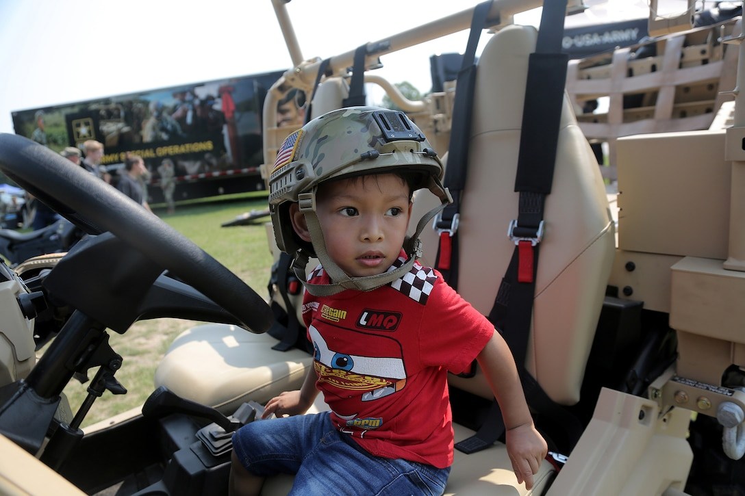 Michael Taylor, 3, pauses for a photo in an Army Polaris MRZR 4 during the Fourth of July NASCAR Cup Series race at Road America, Elkhart Lake, Wisconsin, July 4, 2021.