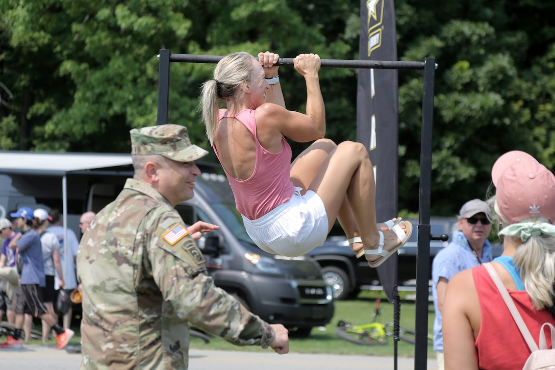 Renee Eckberg, a fitness coach from Oakfield, Wisconsin, performs Army Leg Tucks, one of six events in the U.S. Army's new Army Combat Fitness Test, during the Fourth of July NASCAR Cup Series race at Road America, Elkhart Lake, Wisconsin, July 4, 2021.